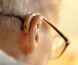 Closeup of hearing aid on back of man's ear.