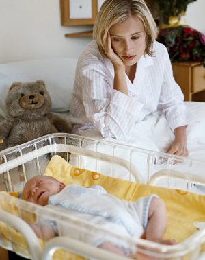 Woman sitting on bed looking at newborn in crib.