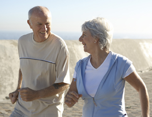 Senior couple walking briskly on beach, smiling.