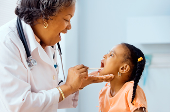 Doctor examines throat of young girl