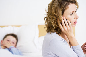 Woman talking on phone, boy in bed in background.