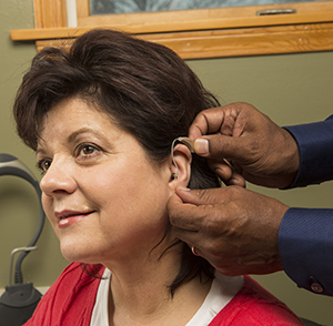 Woman being fitted with hearing aid.
