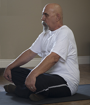 Man sitting in yoga position.