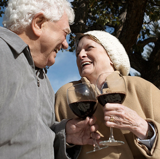 Two senior adults clinking glasses of wine together.