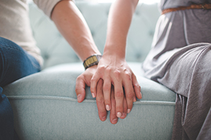 Closeup of man and woman holding hands while sitting on a couch.