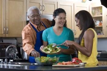 Family making a salad together. Mom is serving the daughter and the father is stealing a vegetable from the bowl