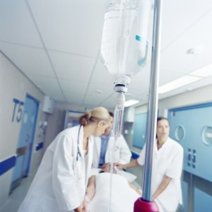 Image of a man on a gurney being wheeled down a hallway at a hospital