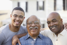 Three generations of African-American men smiling at the camera