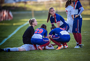 Group of female soccer players and referee gathered around an injured player