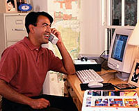 Picture of a man working on the computer, talking on the phone