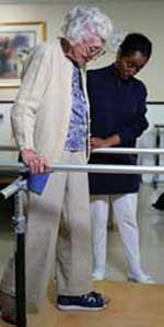 Picture of an elderly woman, walking, during a physical therapy session