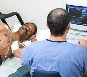 Man lying on side on exam table. Health care provider is holding transducer to skin of man's chest and looking at echocardiogram monitor.