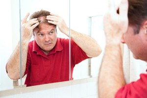Man checking for thinning hair in the mirror.
