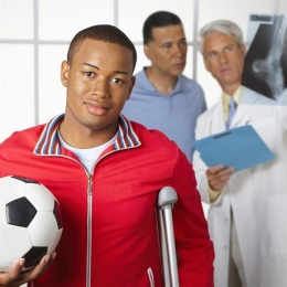 Photo of young man with crutches and a soccer ball
