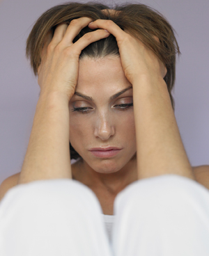 Close-up of woman feeling sad, holding her head.