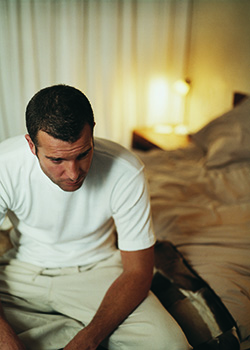 A man in pajamas is sitting on the side of a messy bed. He looks tired.