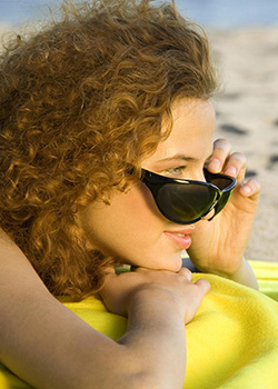 Young woman laying on a beach towel on the beach. She's peering over the top of her sunglasses.