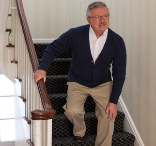 Older man holding a knee as he walks down stairs