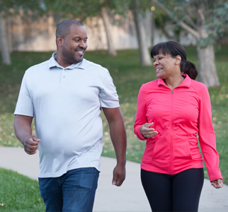 Man and women outdoors, walking for exercise