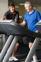 Athletic trainer helps man who is on a treadmill