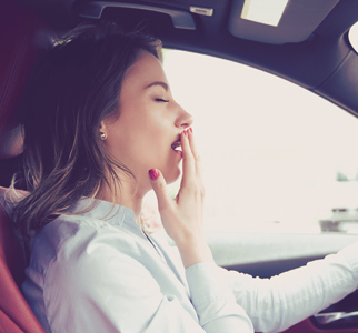 Woman behind wheel of automobile, yawning