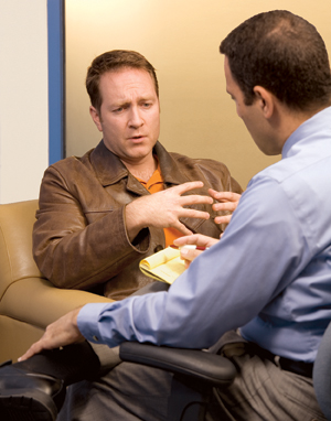 Man sitting and talking to healthcare professional.