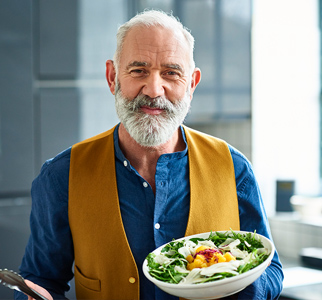 Older man holding a serving bowl of salad